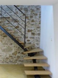 Départ d'escalier quart tournant avec limon en tube acier 120x120 et marches en chêne.