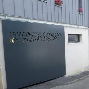 Portail coulissant suspendu en acier et aluminium avec motifs. position fermé