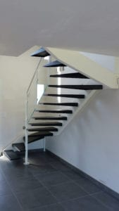 Escalier deux quart tournant avec un limon décalé en tube acier et des marches en tôle pliée.