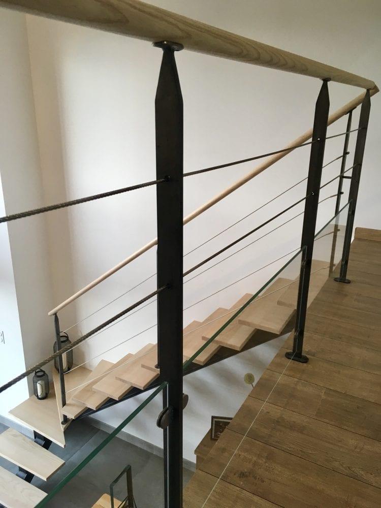 Garde-corps composée de poteaux en fer plat acier, d'une main courante en frêne, d'un soubassement en verre et de deux lisses en câble inox