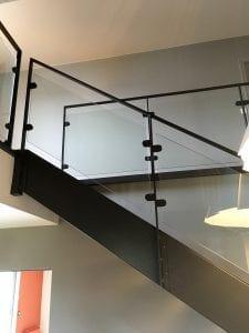 Garde -corps d'étage et rambarde d'escalier composés de poteaux et main courante en fer plat acier et de remplissage en verre