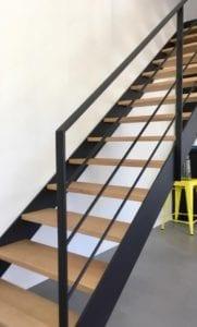 Escalier droit composé de deux limons en tôle acier et de marches en chêne. Garde-corps composé de poteaux et main courante en fer plat acier et de quatre lisses en rond acier