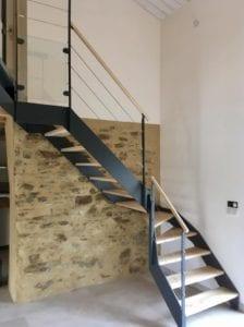 Escalier quart tournant avec deux limons en tôle et marches en frêne. Garde-corps composé de poteaux en fer plat acier, d'une main courante en frêne et de lisses en câble inox